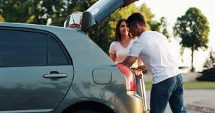 Les couples heureux sont arrivés au tour d'été de vacances en la voiture Obtenez le bagage hors de la voiture clips vidéos