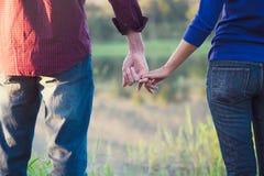 Les couples heureux tenant des mains ensemble comme aiment pour toujours Photographie stock