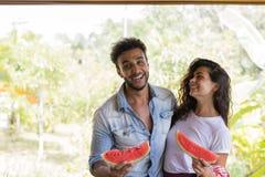 Les couples heureux tenant la tranche de pastèque dans des mains étreinte gaie d'homme et de femme apprécient la pastèque dehors Photo libre de droits