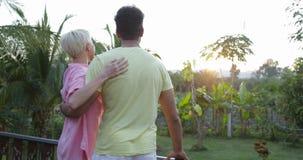 Les couples heureux tournant à la terrasse embrassant au coucher du soleil dehors mélangent le paysage de regard gai d'homme et d banque de vidéos