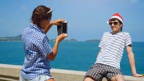 Les couples heureux utilisent le chapeau du ` s de Santa prenant la photo avec le smartphone sur la plage célébrant Noël et la no Images libres de droits