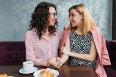 Les couples homosexuels de jeunes amies attirantes de femmes dans l'amour boivent du café image stock