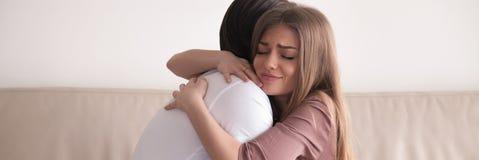 Les couples horizontaux de photo se reposant sur étreindre de divan réconcilient après querelle photographie stock libre de droits