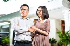 Couples asiatiques de propriétaire d'une maison devant la maison Image libre de droits