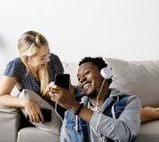 Les couples interraciaux partageant la musique concept aiment à la maison, de loisirs et de musique Images stock