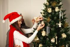 Les couples joyeux dans des chapeaux rouges décorent l'arbre de Noël Photos stock