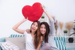 Les couples lesbiens de lgbt de l'Asie tenant le coeur rouge se reposent ensemble plus de Photos libres de droits
