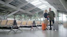 Les couples mariés avec des valises sont à l'intérieur de hall de attente de station pendant la journée banque de vidéos