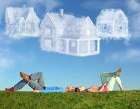 Les couples menteur sur l'herbe et le rêve trois opacifient des maisons Photographie stock