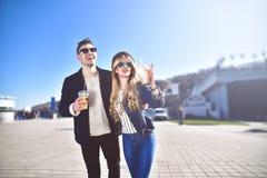 Les couples mignons marchant à la rue et boivent des cocktails photos stock