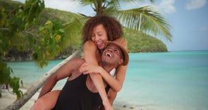 Les couples millénaires d'afro-américain se donnent des tours de ferroutage par la plage Photographie stock libre de droits