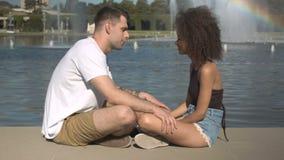 Les couples multi-ethniques romantiques détendant par l'eau en été se garent clips vidéos