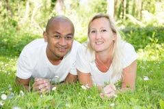 Les couples multi-ethniques se trouvant sur le jardin d'herbe verte se garent dans la femme blonde d'amour et l'homme indien Images stock
