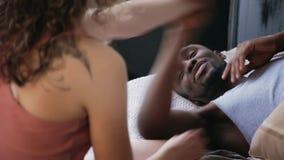 Les couples multi-ethniques sur le lit, combat par des oreillers, ont l'amusement ensemble Femme dans des pyjamas se reposant sur banque de vidéos