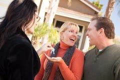 Les couples obtiennent des clés de Chambre de l'agent hispanique Image stock