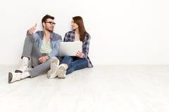 Les couples occasionnels discutent quelque chose qui se repose avec l'ordinateur portable, tir de studio Image stock