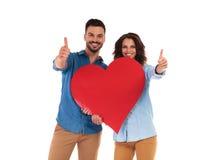 Les couples occasionnels heureux tenant le coeur et font le signe correct Photographie stock