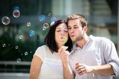 Les couples ont l'amusement avec le ventilateur de bulle Photos stock