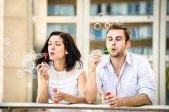 Les couples ont l'amusement avec le ventilateur de bulle Photo libre de droits