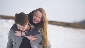 Les couples ont l'amusement extérieur - le jeune homme donnant a continue le sien dos son amie heureuse Image libre de droits