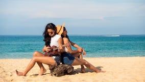 Les couples ou les amis intimes lesbiens jouent l'ukulélé et se reposent sur la plage Photos libres de droits