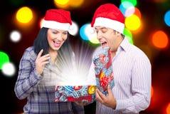 Les couples ouvrent un cadeau magique de Noël Photographie stock libre de droits