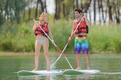 Les couples parfaits de silhouette engagent l'embarquement standup de palette Images stock