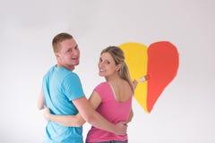 Les couples peignent un coeur sur le mur image libre de droits