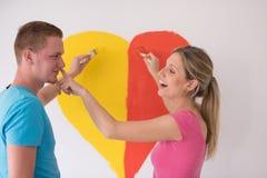 Les couples peignent un coeur sur le mur photographie stock