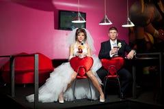 les couples pendant le jour du mariage se reposant dans les chaises de rouge avec le coeur dans le cocktail de pièce et de boisso Photo libre de droits