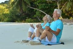 Les couples pluss âgé méditent sur la plage Photo libre de droits