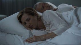 Les couples pluss âgé se situant dans le lit éveillé, femme l'ont tournée de nouveau à l'homme, ressentiment banque de vidéos