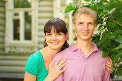 Les couples posent près de la maison en bois de village Photo stock