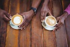 Les couples remettent tenir la tasse de café Images stock
