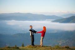 Les couples romantiques appréciant un matin harassent au-dessus des montagnes Photo stock
