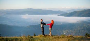 Les couples romantiques appréciant un matin harassent au-dessus des montagnes Photos stock