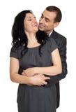 Les couples romantiques dans l'amour, habillé dans le costume noir, ont isolé le blanc Photos stock