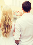 Les couples romantiques dans la ville faisant le coeur forment Photo stock