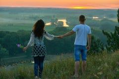 Les couples romantiques marchent sur la colline au coucher du soleil sur le pays extérieur, la fille avec le bouquet de la fleur  Photos libres de droits