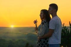 Les couples romantiques regardent sur le soleil, même sur les terres extérieures et belles Images libres de droits