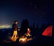 Les couples romantiques s'approchent du feu de camp la nuit étoilé Images stock
