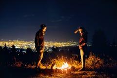 Les couples romantiques s'approchent du feu de camp la nuit Photos libres de droits