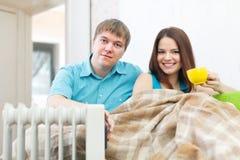 Les couples s'approchent de l'appareil de chauffage d'huile Images stock