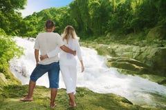 les couples s'approchent de la cascade à écriture ligne par ligne Photos stock
