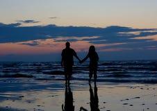 Les couples s'approchent de la mer au coucher du soleil. Photo libre de droits