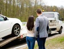 Les couples s'approchent de la voiture cassée sur un bord de la route Photos libres de droits
