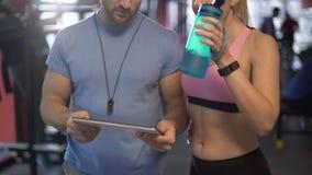 Les couples sains discutant la séance d'entraînement prévoient dans le gymnase, définissant de futurs buts de forme physique banque de vidéos