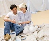 Les couples se reposant avec la peinture peuvent et l'échantillon de couleur Photo libre de droits