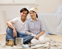 Les couples se reposant avec la peinture peuvent et l'échantillon de peinture Photographie stock