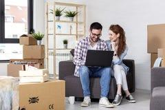 Les couples se reposant sur le sofa et lui travaillent sur l'ordinateur photo libre de droits